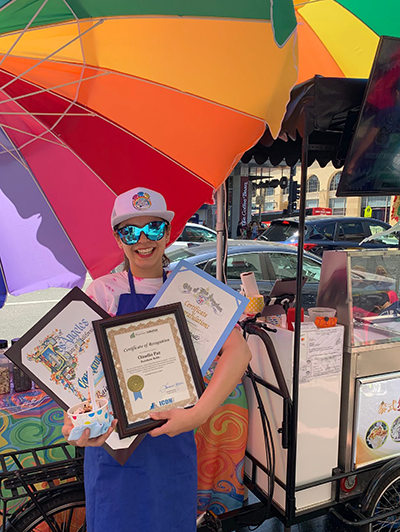 Claudia Paz poses next to her non-dairy vegan ice cream cart with framed Business Certificates of Recognition from the City of Los Angeles and EWDD partner ICON CDC