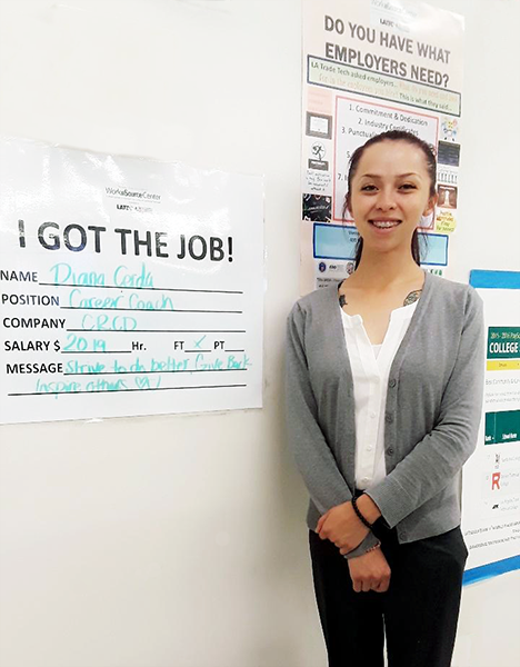 WorkSource program participant Diana stands beside the sign announcing her new job as a career coach at the Vernon-Central/Los Angeles Technical Trade College WorkSource Center